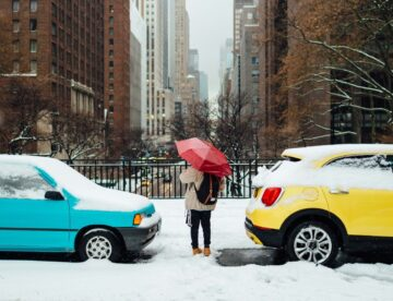 person standing in between yellow and blue cars covered with snow